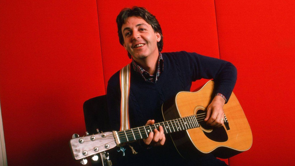 Portrait of British musician Paul McCartney as he plays acoustic guitar against a red background, October 7, 1984 . Crédits : Robert R. McElroy