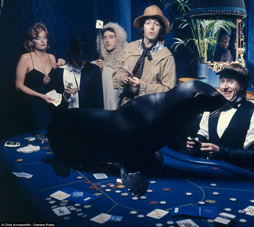 Promo shot for Junior's Farm single release. Wings pose for a casino-inspired photo in 1974 (pictured Linda McCartney, Denny Laine, Sir Paul McCartney: Jimmy McCulloch and Joe English). Arrowsmith said of the images: 'They really capture the seminal moments of the shoot... The fun we were all having, plus Paul and Linda's closeness, it's the naturalness of the pictures that is the key to their success'