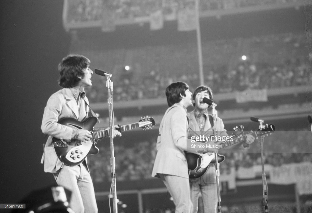 The Beatles live at Shea Stadium, New York, August 23, 1966. L-R George Harrison (playing a Rickenbacker 260/12 12 string guitar), Paul McCartney and John Lennon.