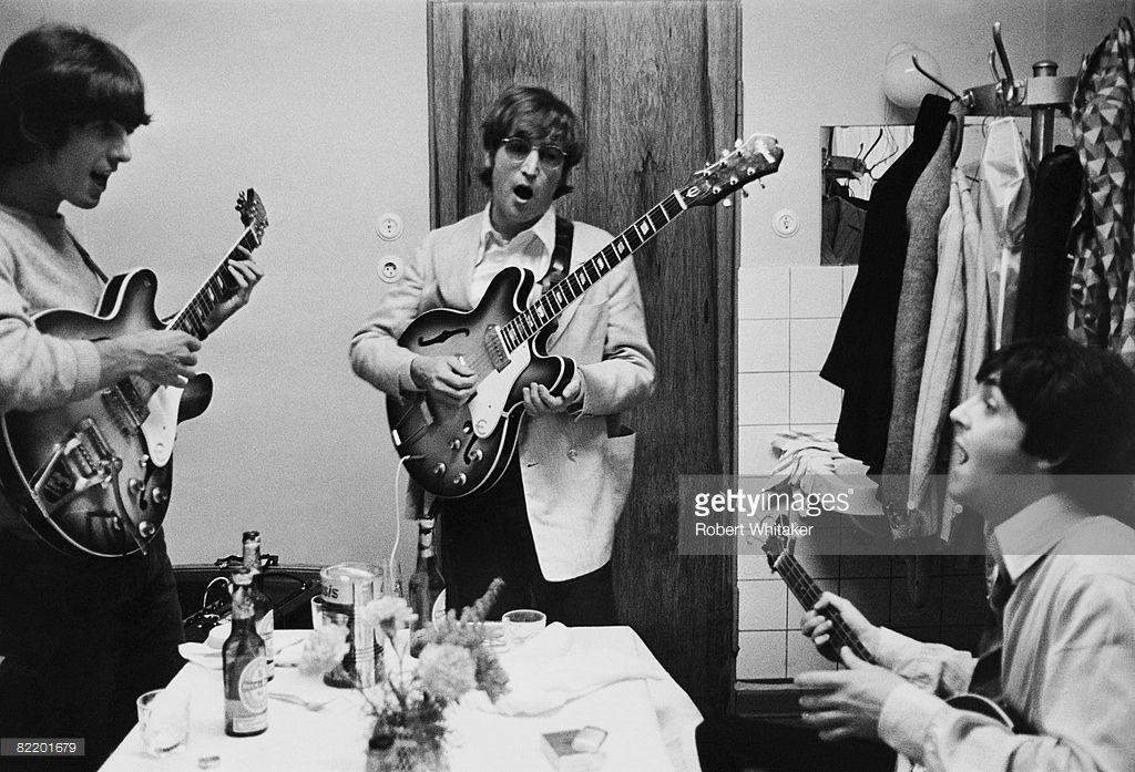George Harrison (1943 - 2001), John Lennon (1940 - 1980) and Paul McCartney of the Beatles tuning up backstage before a concert at the Ernst Merck Halle, Hamburg, during their last world tour, 26th June 1966.