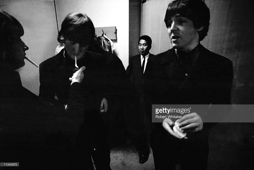 Ringo Starr lights John Lennon's cigarette backstage at the Budokan Hall, Tokyo, Japan. They are with and Paul McCartney and promoter Tatsuji Nagashima is in the background, 30th June 1966 - Credit: Robert Whitaker