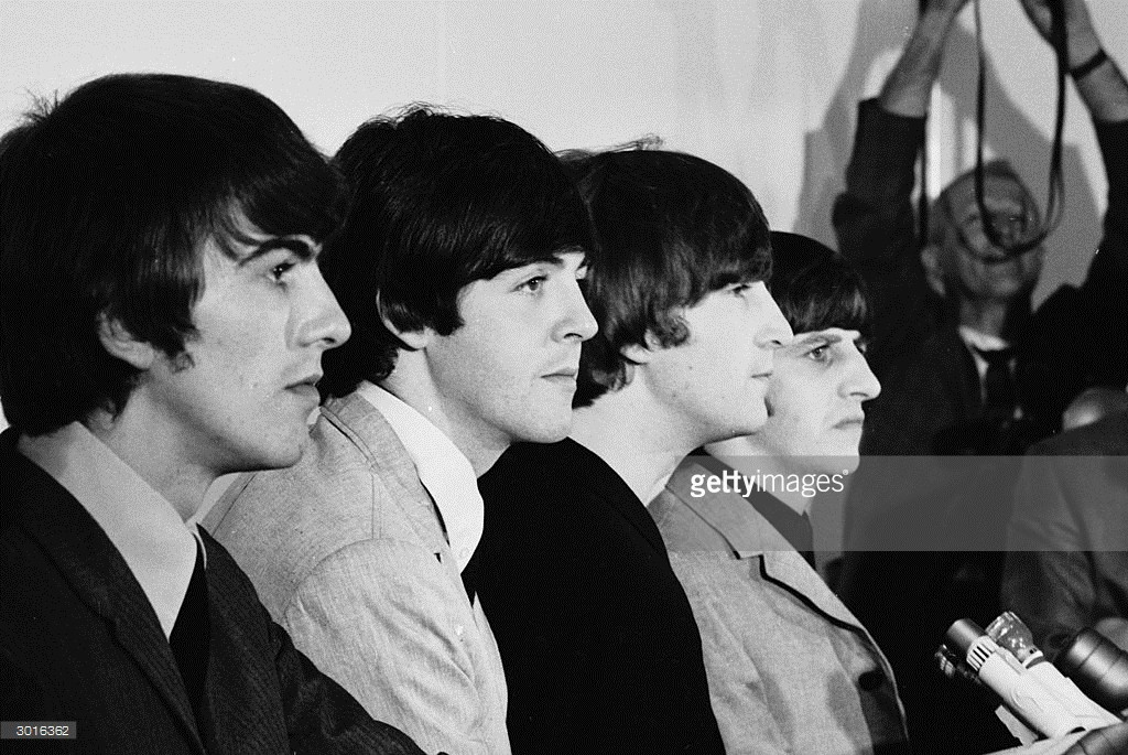 British pop group the Beatles, (L-R) George Harrison (1943 - 2001), Paul McCartney, John Lennon (1940 - 1980), and Ringo Starr listen to questions at a press conference, San Francisco, California, August 1964.