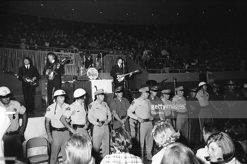 A line of police officers prevent fans from getting too close, as The Beatles perform behind them on stage at the Convention Hall, Las Vegas.