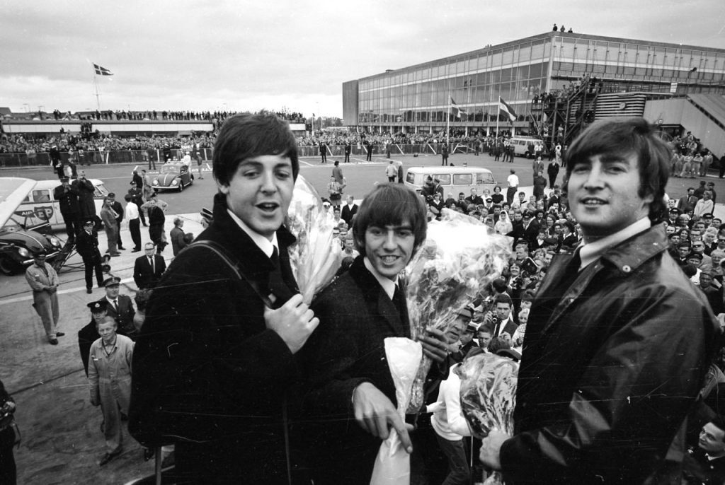 The Beatles ankommer til Kastruo for at give koncert i KB-hallen. Her ses de tre af dem, Poul McCartney, George Harrison og John Lennon.; The English rockband arrives in Kastrup Airport to play in KB-hallen. Here photographed Paul McCartney, George Harrison and John Lennon.